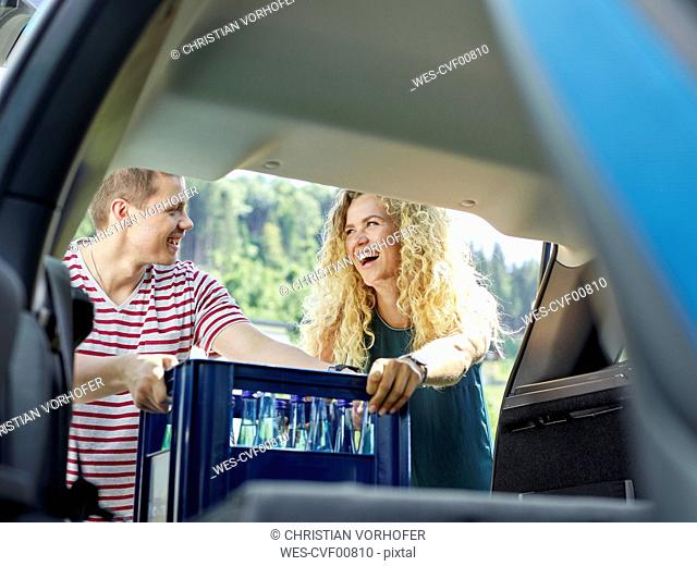 Happy couple loading boot of electric car