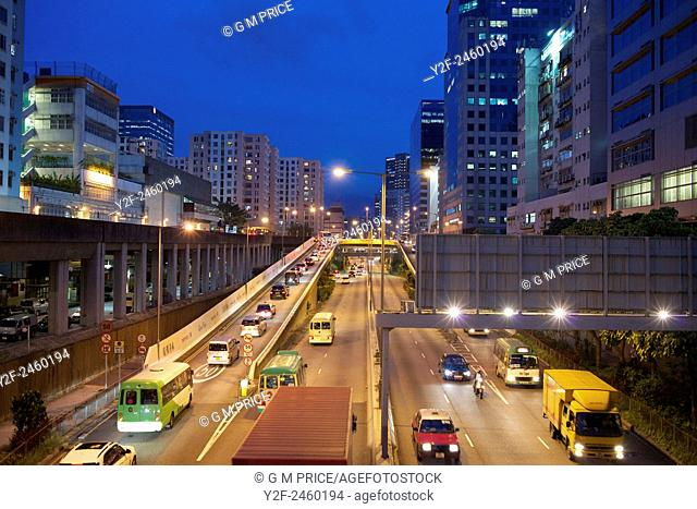 busy motorway and apartments at dusk in Kowloon Bay, China