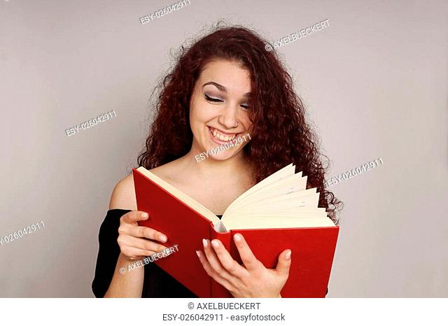 smiling teenage girl enjoys reading a funny hardcover book