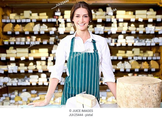 Shop owner standing with large variety of cheeses