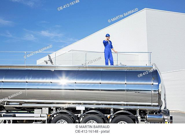 Worker talking on cell phone on platform above stainless steel milk tanker