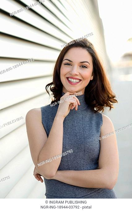 Young woman wearing casual clothes smiling in urban background. Girl with beautiful smile