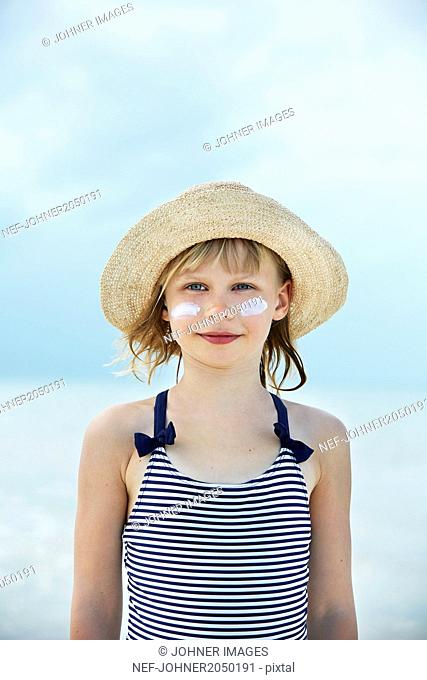 Portrait of girl with face cream by sea
