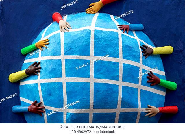 Hands with different skin colours reaching for a globe made of papier-mâché, theme car, symbol against racism and for tolerance, Carnival Monday procession