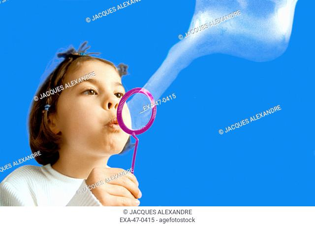 Studio shot of young girl blowing bubbles