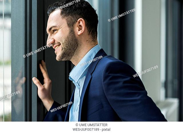 Businessman smiling, standing on window
