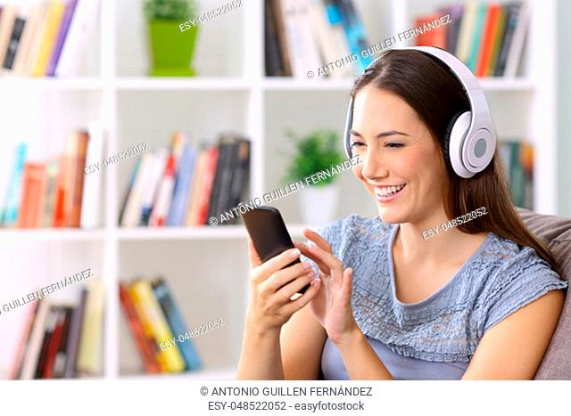 Happy female listening to music on line with a smart phone and headphones sitting on a couch at home