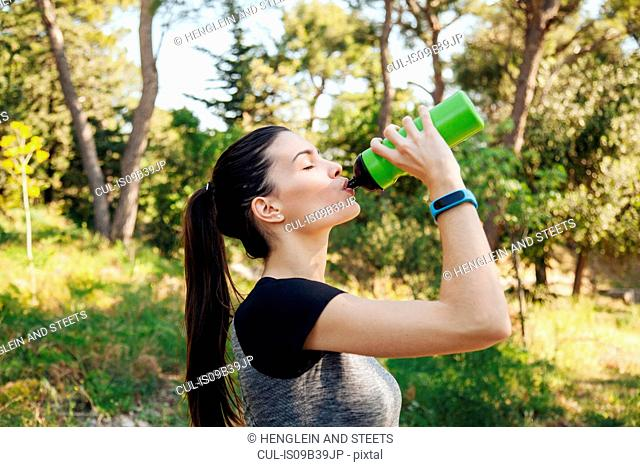 Female runner drinking water bottle in park, Split, Dalmatia, Croatia