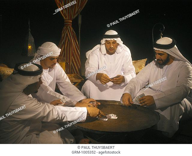 Arab men playing cards in Arabian tent