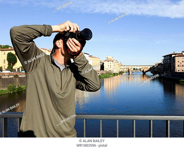 Italy, Florence, Man using camera on bridge over River Arno