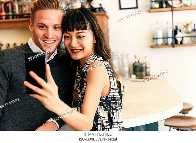 Young couple taking smartphone selfie in cocktail bar