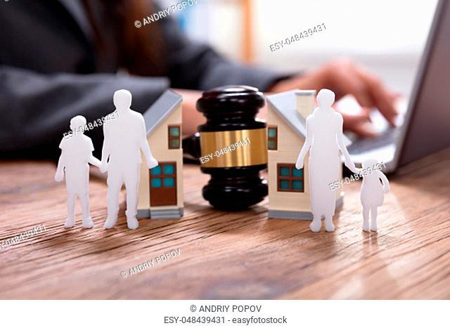Close-up Of Gavel Between Split Family Figures And House Model With Business Person Using Laptop