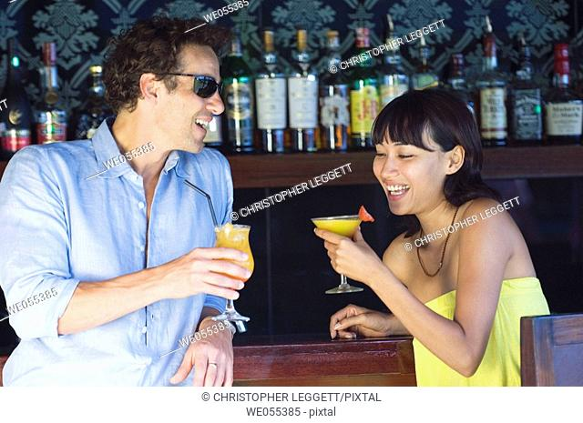 young couple talking and drinking at bar