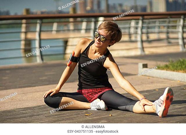Chinese young woman warming up for jogging in city park