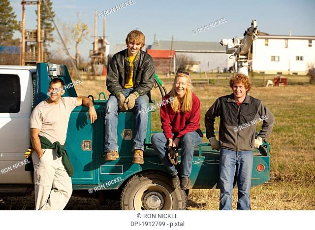 a group of people sitting on the back of a truck, three hills, alberta, canada