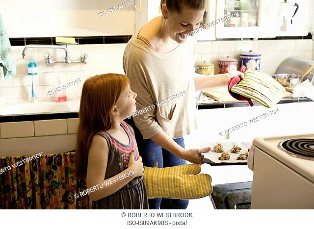 Girl and mid adult mother baking biscuits