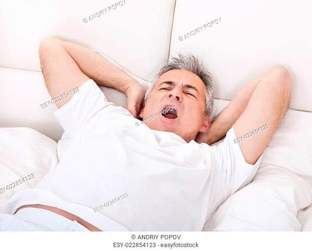 Yawning Mature Man Stretching His Arm
