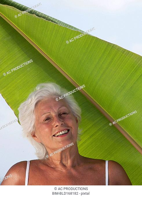 Older Caucasian woman standing under leaf