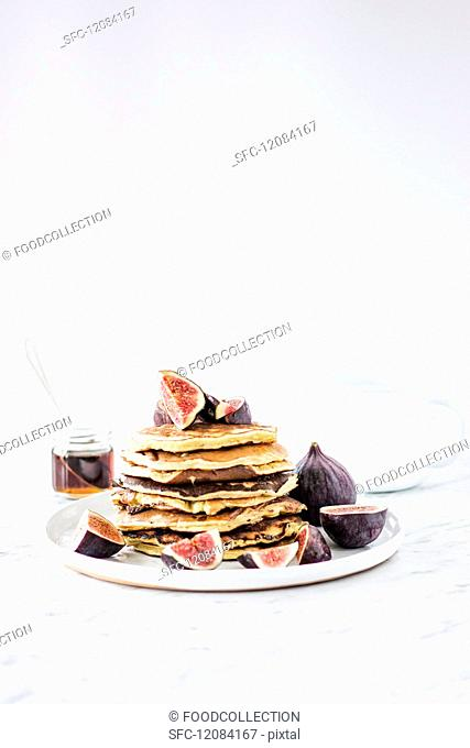 A pile of pancakes with figs and maple syrup