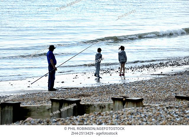 Bexhill-on-Sea, East Sussex, England, UK. Man fishing on the beach and two children walking past