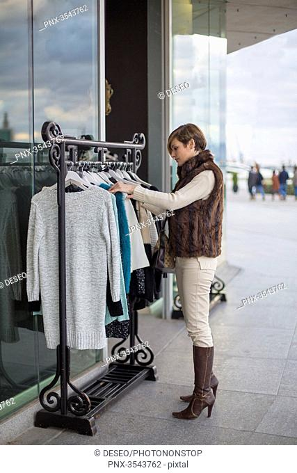 Woman searching fot clothes in a store outside