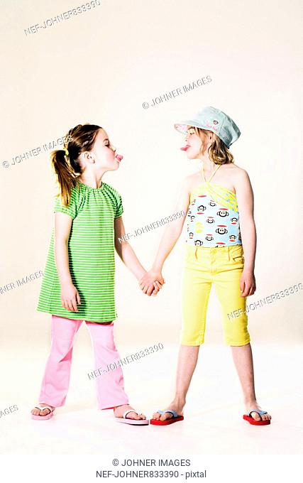 Two girls holding hands and sticking their tongues out