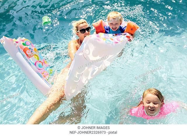 Mother with children in swimming-pool
