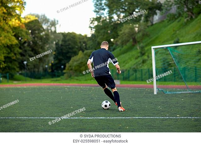 sport, football training and people - soccer player playing with ball on field