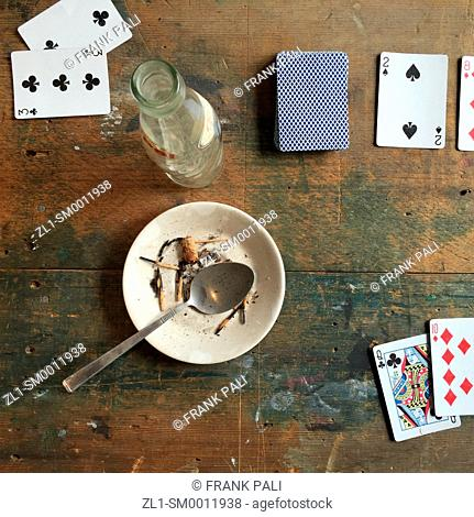 Old dirty table with playing cards and dirty plate with spoon