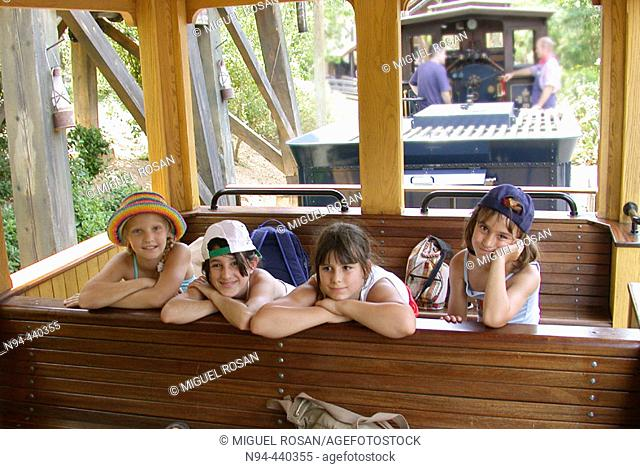 4 girls between 8 and 10 years with a trip by train in the Port Aventura theme park in Tarragona. Catalunya, Spain