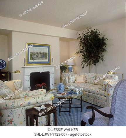 LIVING ROOMS - TraditionaL in peach and florals, fireplace, blue patterened carpet, ficus tree, glass tray style coffee table, ginger jar
