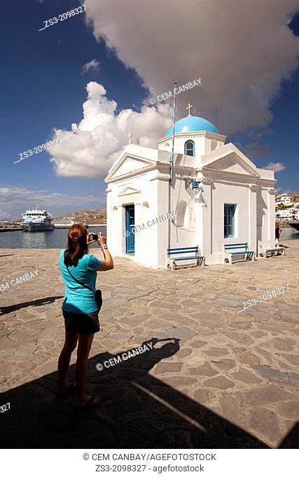 Woman taking photo of the blue domed church, Little Venice, Mykonos, Cyclades Islands, Greek Islands, Greece, Europe