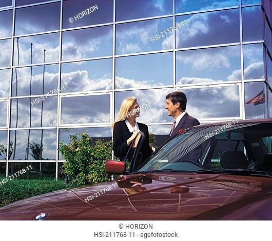 Businesspeople standing with car by building in United Kingdom, Europe