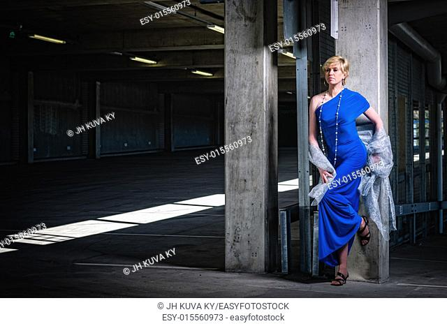 Beautiful mature woman wearing blue dress and posing in public parking house