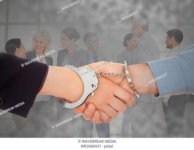 Handshake with handcuffs in front of business people with grunge overlay