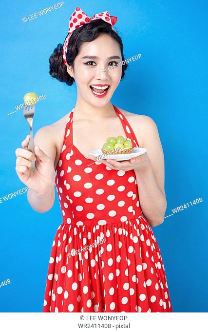 Young smiling woman in retro style posing with green grapes and a fork staring at front