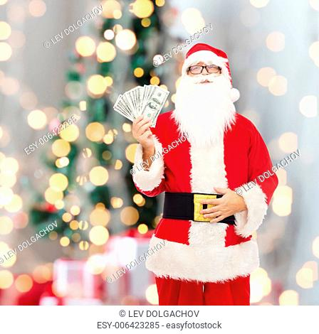 christmas, holidays, winning, currency and people concept - man in costume of santa claus with dollar money over tree lights background