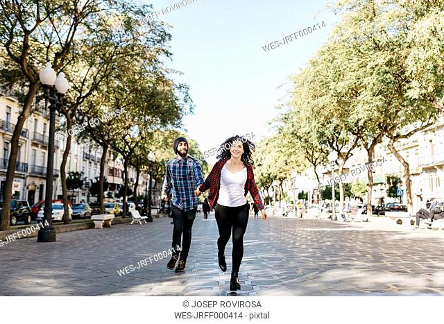 Spain, Tarragona, happy young couple running in the city