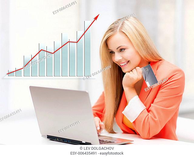 people, business, technology, e-commerce concept - smiling businesswoman with laptop and credit card in office