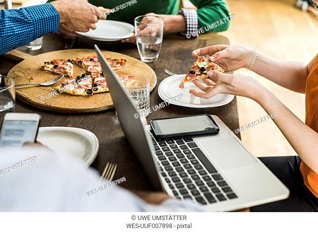 Colleagues at table with cell phone and laptop having a pizza