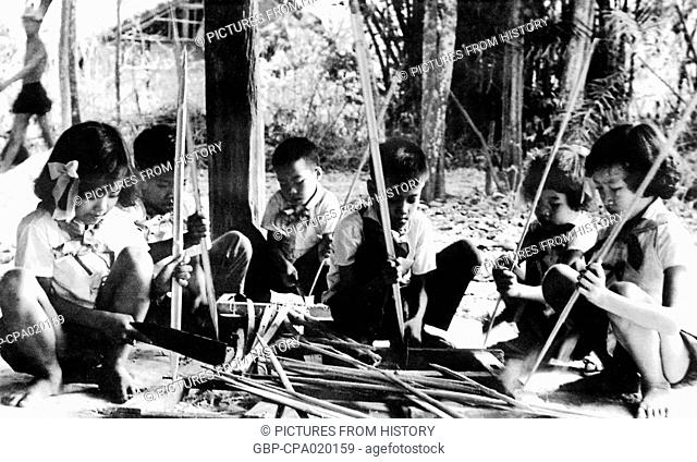 Vietnam: Children help whittle bamboo spikes, Cu Chi, South Vietnam, Second Indochina War (Vietnam War) (1968)
