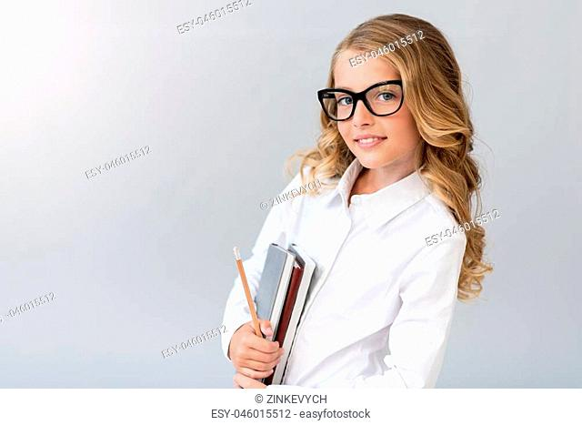 I plan my career. Smiling confident little girl with glasses looking at the camera while standing with a pencil and notebooks on the grey background