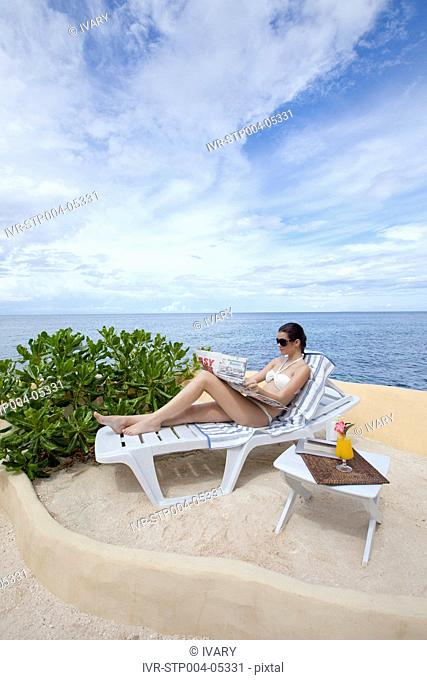 A young woman reading in a deck chair by the ocean