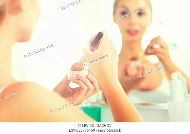 beauty, make up, cosmetics, morning and people concept - close up of young woman makeup brush and powder foundation looking to mirror at home bathroom