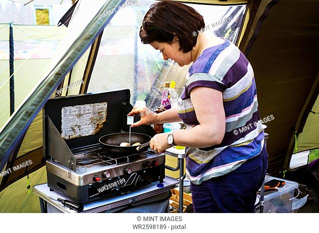 Woman standing at a camping stove, measuring the temperature of a scallop in a frying pan with a digital thermometer