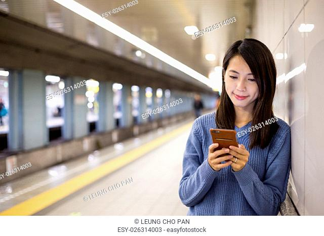Woman use of cellphone in underground metro station