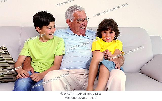 Senior man sitting on couch with his grandsons at home in the living room