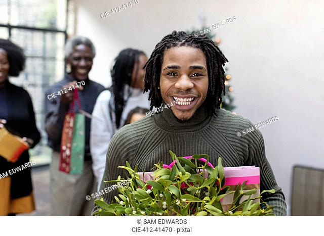 Portrait smiling, enthusiastic young man with Christmas gift and mistletoe