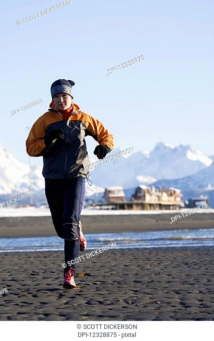 A Young Woman Jogs On The Wet Beach; Homer, Alaska, United States Of America
