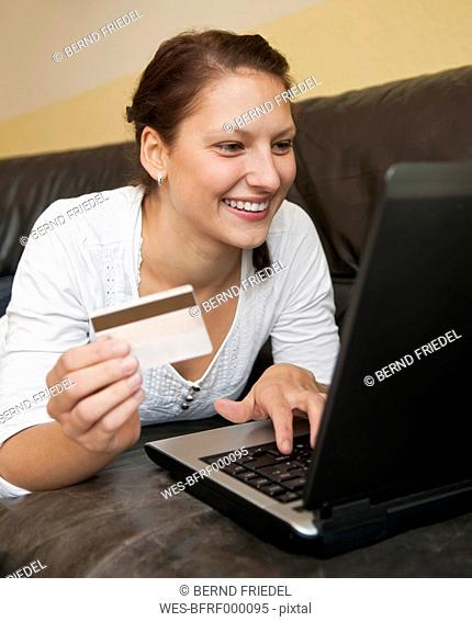 Germany, Brandenburg, Young woman shopping online from home with laptop and credit card